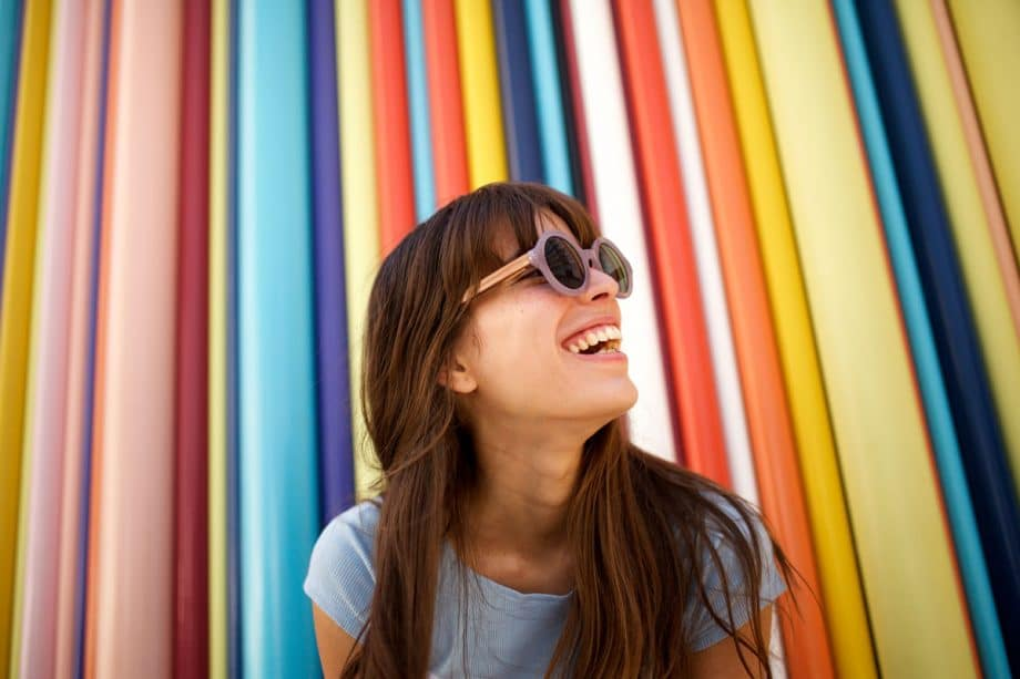 woman sitting in front of colorful striped background, smiling and wearing round purple sunglasses